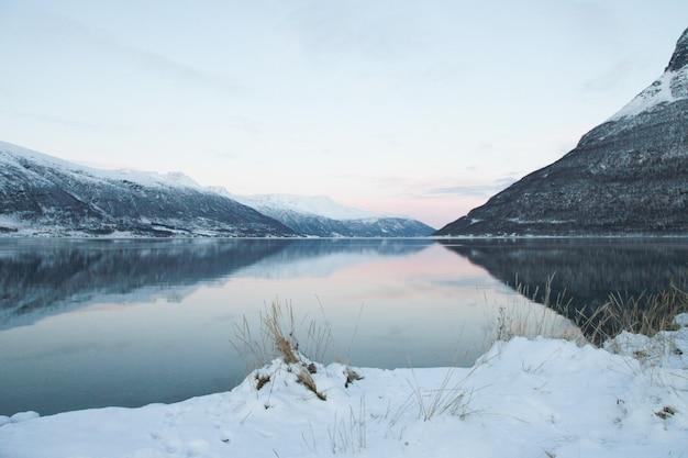Paysage panoramique avec des arbres enneigés, soleil, belle rivière gelée avec reflet dans l'eau