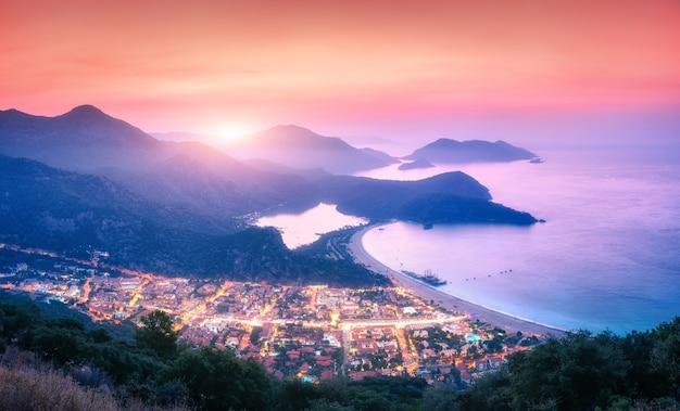 Paysage panoramique avec lagon bleu, mer, lumières de la ville, montagnes dans le brouillard, ciel coucher de soleil rouge, nuages. belle oludeniz au crépuscule en turquie en été. vue de dessus de la montagne la nuit. voyager en europe
