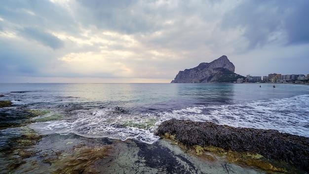 Paysage panoramique sur la mer avec une grande montagne à l'horizon et des vagues se brisant contre les rochers.