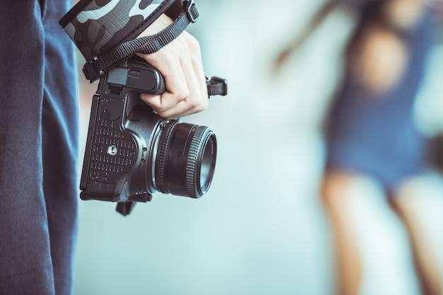 Paysage de photographe professionnel avec appareil photo reflex numérique dans les mains d'une femme intelligente, prête à prendre des photos, les photographes prennent des instantanés pour le plaisir de se souvenir d'événements, ton vintage