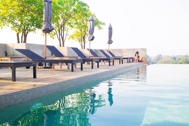 Paysage de piscine sur le toit avec femme asiatique relaxante