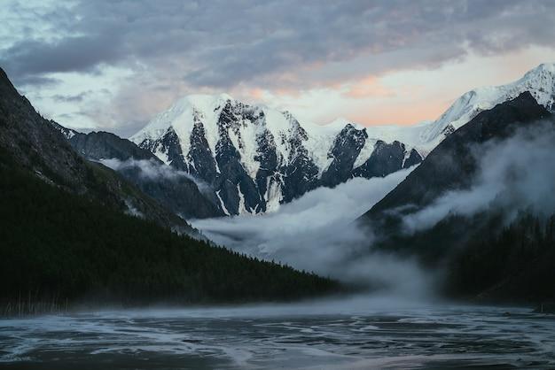 Paysage pittoresque avec de grandes montagnes enneigées au coucher du soleil et des nuages bas et denses dans une vallée de montagne avec une silhouette de forêt. paysages atmosphériques avec une haute montagne enneigée au lever du soleil et d'épais nuages bas