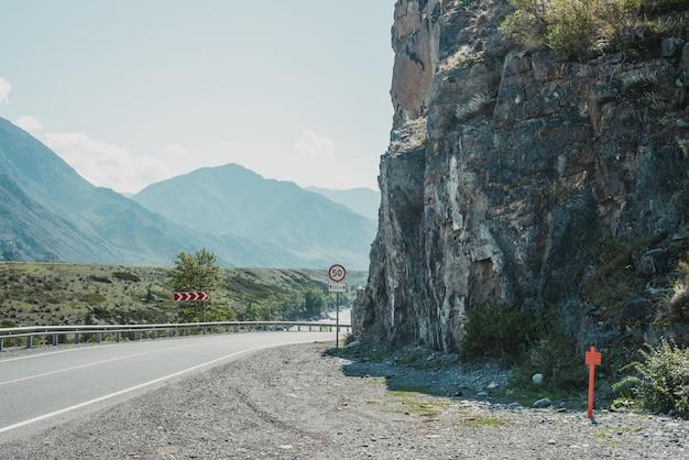 Paysage pittoresque avec panneau de signalisation de limitation de vitesse sur la route de montagne. vue latérale pour tracter dans les hautes terres. beau paysage avec route goudronnée avec marquage routier. autoroute avec ligne continue et rivière de montagne.