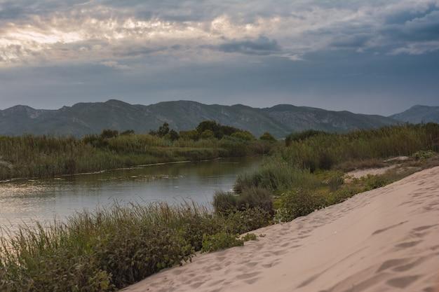 Paysage plage de montagne le long de la rivière au coucher du soleil iwith ciel violet n xeraco, valence