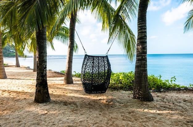 Paysage d'une plage tropicale avec des palmiers. chaise pivotante sur les palmiers.