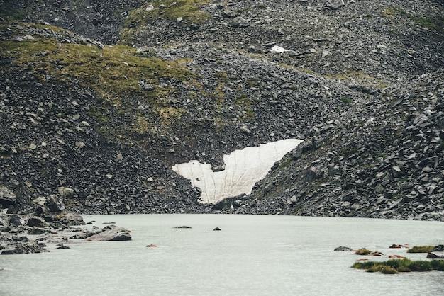 Paysage pluvieux sombre avec des cercles de pluie sur la surface de l'eau du lac de montagne. paysage de montagne atmosphérique avec lac de montagne parmi les moraines par temps de pluie. belle vue sombre sur le lac glaciaire.