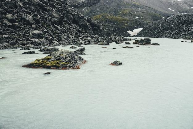 Paysage pluvieux sombre avec des cercles de pluie sur la surface de l'eau du lac de montagne. paysage de montagne atmosphérique avec lac de montagne parmi les moraines par temps de pluie. gros rocher avec de la mousse dans le lac glaciaire.