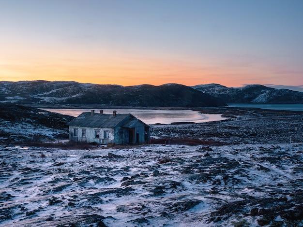 Paysage polaire du soir avec une vieille maison à côté d'un lac