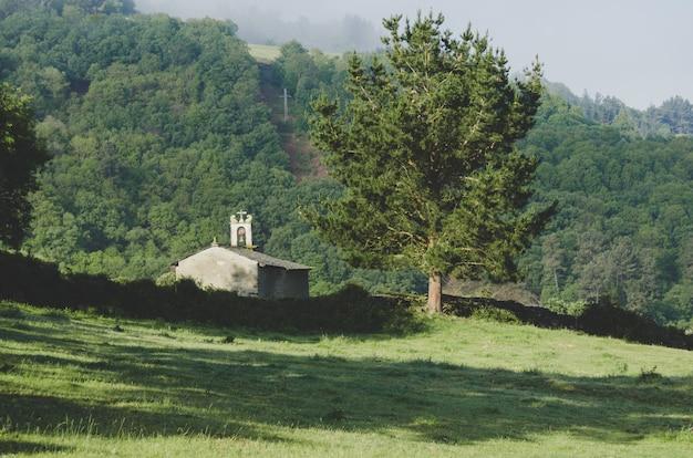 Paysage de prairies avec église en arrière-plan.