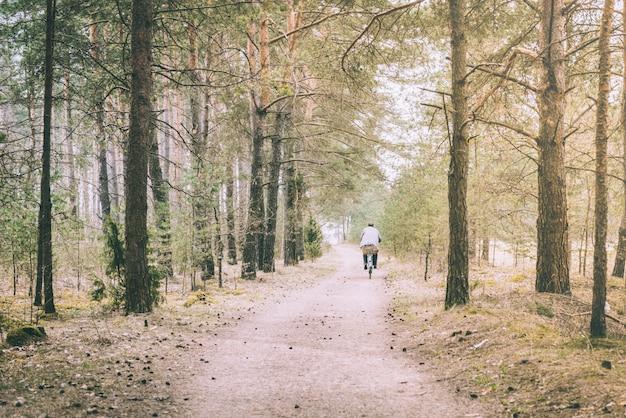 Paysage de printemps du chemin forestier. humain à vélo.