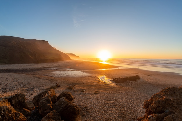 Paysage d'un rivage entouré de montagnes et de la mer sous un ciel bleu au coucher du soleil