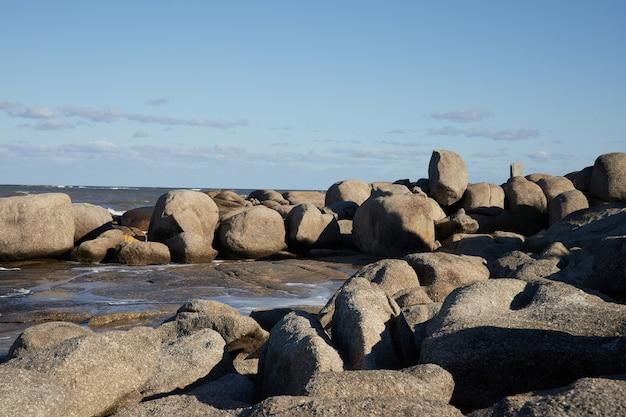 Paysage de rochers sur l'eau sur la côte de l'océan, sous le ciel bleu avec des nuages.