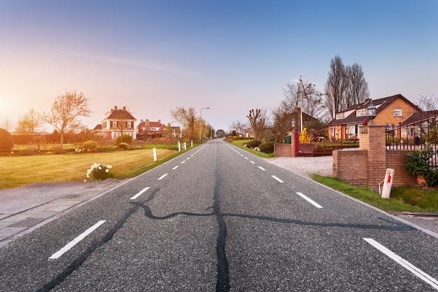 Paysage avec route goudronnée à travers la ville au coucher du soleil