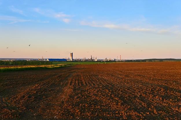 Paysage rural avec des champs labourés et une usine chimique à l'horizon
