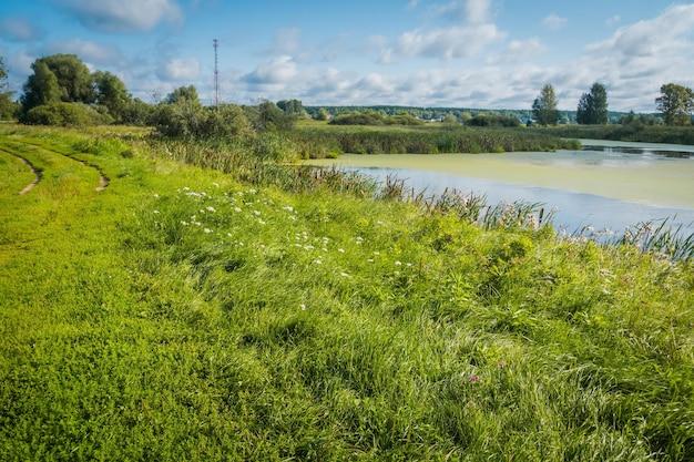 Paysage rural d'été avec rivière et fond de ciel bleu.