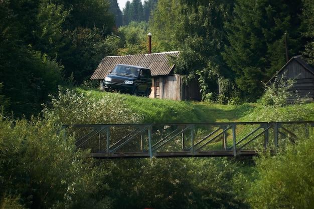 Paysage rural, une ferme isolée dans la forêt - une cabane en rondins, un bain public et un véhicule tout-terrain au bord d'un ravin avec un pont