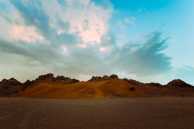 Paysage silencieux du désert de dubaï avec des montagnes et un ciel dramatique