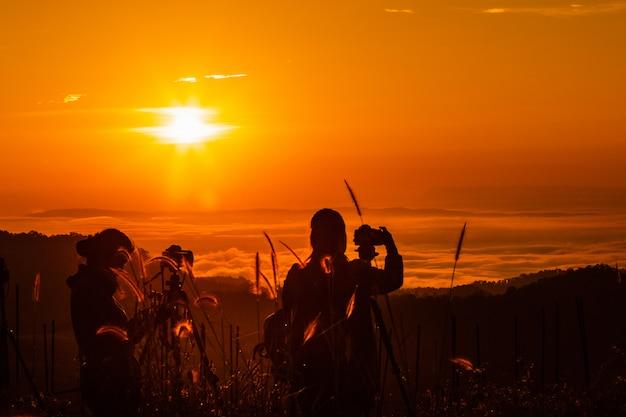 Paysage silhouette au touriste prend des photos du lever et du brouillard sur la montagne