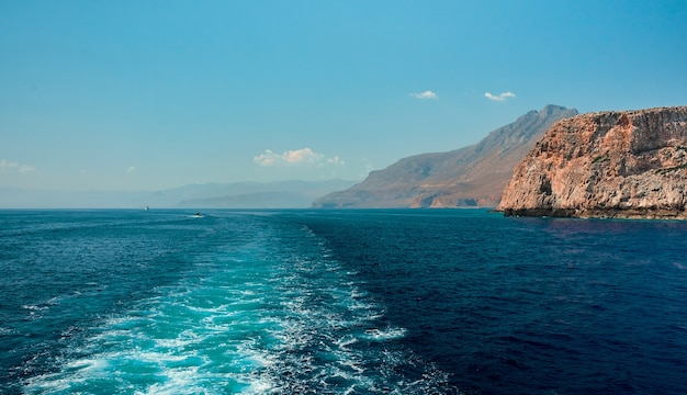 Paysage superbement lumineux de la mer, tourné depuis un bateau à grande vitesse, sur fond de falaises et d'un ciel bleu sans nuages.