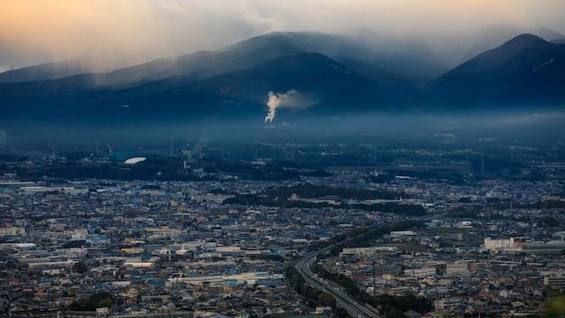 Paysage urbain dramatique et sombre à strom et fond de montagne de couche de smog au japon