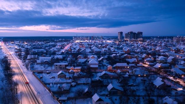 Paysage urbain d'hiver. rues illuminées de la banlieue et chalets.