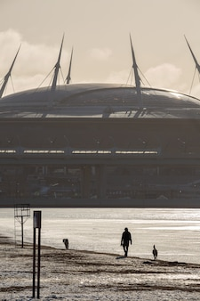 Paysage urbain avec un homme qui marche avec ses chiens devant l'immense bâtiment du stade sous le soleil en hiver saint-pétersbourg, russie.