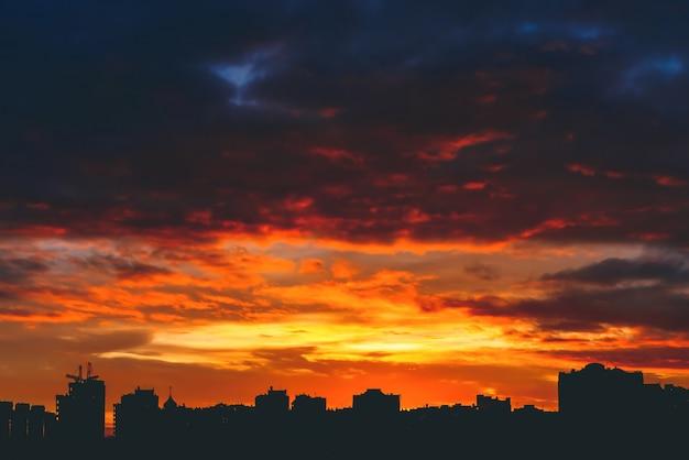 Paysage urbain avec une magnifique aube de feu vive et multicolore. incroyable ciel nuageux multicolore dramatique. silhouettes sombres des bâtiments de la ville.