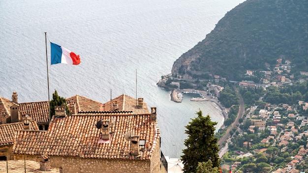 Paysage urbain de menton france toits de bâtiments résidentiels traditionnels avec mer drapeau national