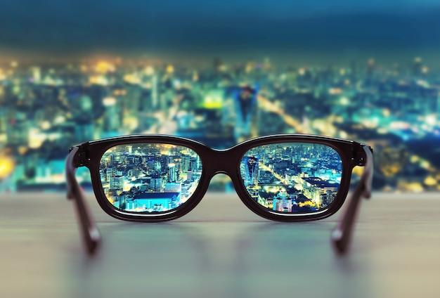 Paysage urbain de nuit concentré dans les verres de lunettes. notion de vision