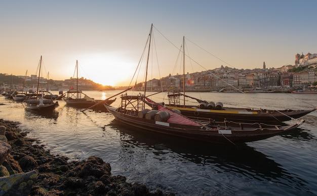 Paysage urbain de porto au coucher du soleil avec rivière à l'avant et navire transporteur de vin en premier plan et ville de porto en arrière-plan, portugal