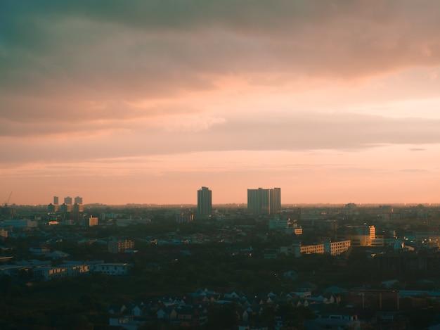 Paysage urbain de la ville inconnue avec des nuages épais et la lumière du coucher du soleil.