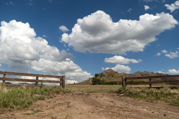 Paysage de vallée avec une clôture en bois ouverte sous le ciel nuageux