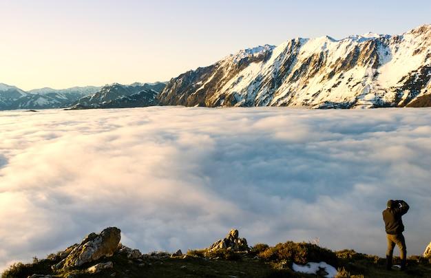 Paysage de vallée de montagne de brouillard et de nuages de neige.