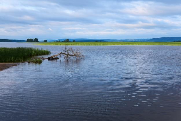 Paysage avec un vaste lac marécageux parmi les collines couvertes de roseaux