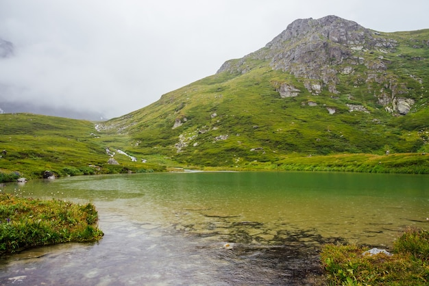 Paysage vert vif avec des gouttes de pluie sur le lac de montagne parmi les nuages bas.