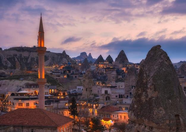 Paysage de la ville de nuit de göreme, cappadoce turquie, donnant sur le minaret et les maisons dans les rochers