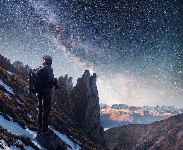 Paysage avec voie lactée, étoiles du ciel nocturne et silhouette d'un homme photographe debout sur la montagne.