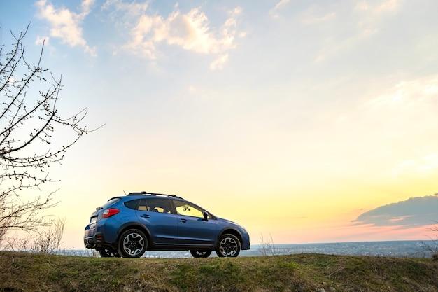 Paysage avec une voiture hors route bleue au coucher du soleil.