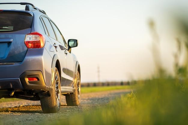 Paysage avec voiture hors route bleue sur route de gravier. voyager en automobile, à l'aventure dans la faune, en expédition ou en voyage extrême en suv. véhicule tout-terrain 4x4 dans le champ au lever du soleil.