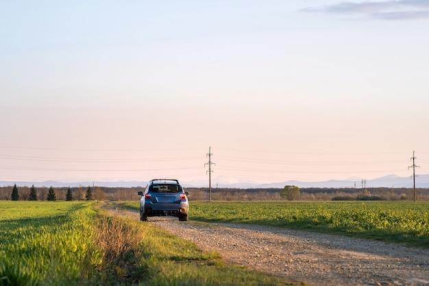 Paysage avec une voiture tout-terrain bleue sur une route de gravier.