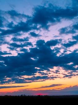 Paysages à couper le souffle de beaux nuages au-dessus d'un champ d'arbres verts