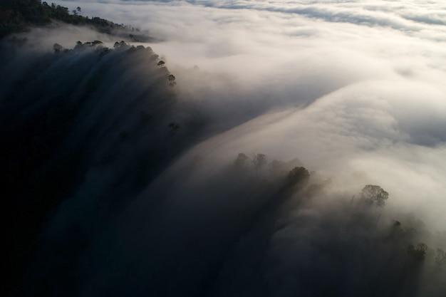 Paysages étonnants nature paysage vue sur la nature vue aérienne de la photographie par caméra drone de la brume ou du brouillard s'écoulant sur le sommet de la montagne le matin au lever ou au coucher du soleil à khao khai nui phang nga en thaïlande.