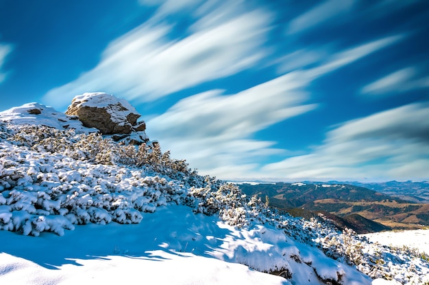 Paysages merveilleux couverts de la première neige avec de grandes corniches rocheuses des montagnes des carpates, ciel bleu clair dans la pittoresque ukraine près du village de dzembronya