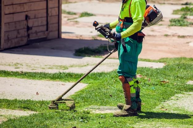 Paysagistes routiers en uniforme coupant l'herbe dans le parc à l'aide de coupe-gazon à cordes.