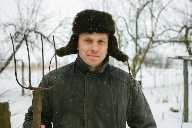 Paysan avec fourche en hiver