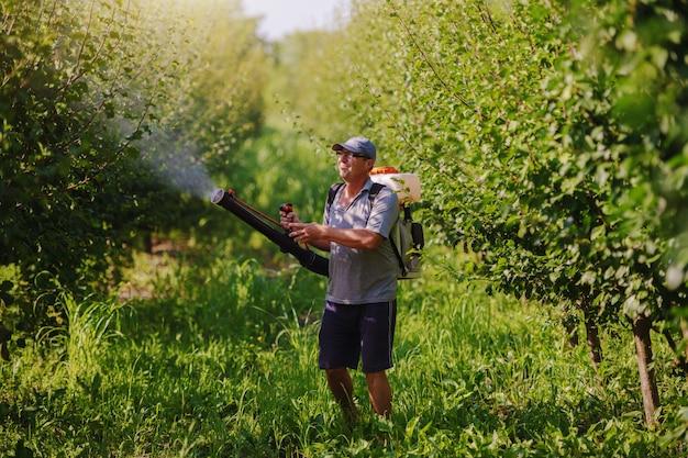 Paysan mature du caucase en vêtements de travail, chapeau et avec une machine de pulvérisation de pesticides moderne sur le dos, pulvérisant des insectes dans le verger