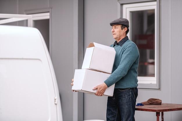 Paysan de race blanche portant des boîtes qu'il veut envoyer.