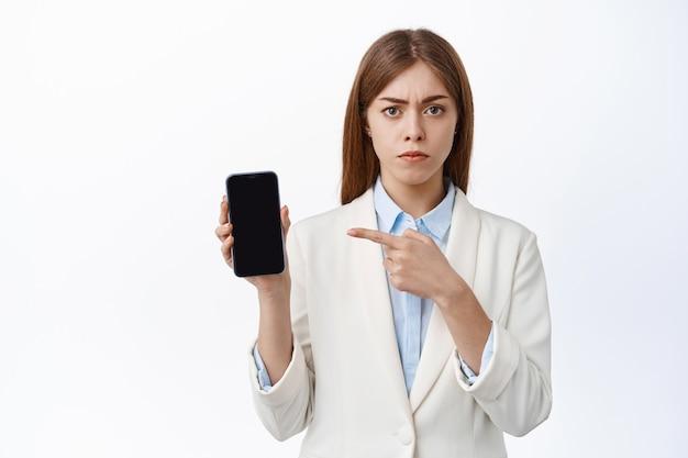 Une pdg de bureau sérieuse et mécontente pointe un écran de smartphone vide, fronçant les sourcils et l'air déçu, debout sur un mur blanc