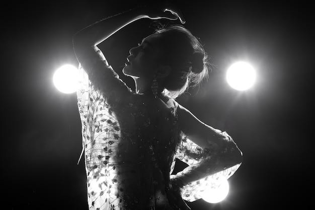 Peau bronzée asiatique slim sexy femme voir à travers une robe de soirée avec de la lumière arrière fumée