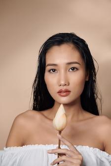 Peau fraîche et naturelle. jolie femme sensuelle à la peau bronzée, tenant des boutons de lotus séchés isolés sur fond beige